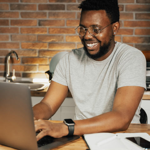 Man, sat at laptop looking happy, possibly having seen success in his work