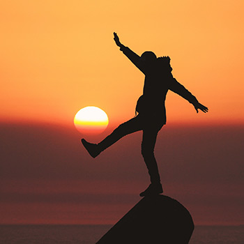 Silhouette of person balancing on a rock