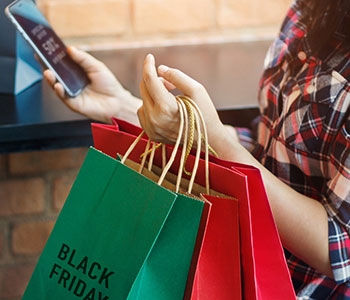"Woman holding ""Black Friday"" shopping bags and phone"