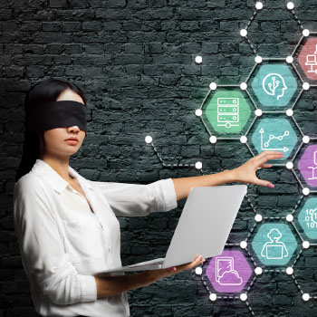 Businesswoman, blindfolded, with laptop reaching out to feel abstract, marketing related icons