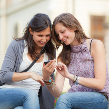 An image of two young women looking at a phone