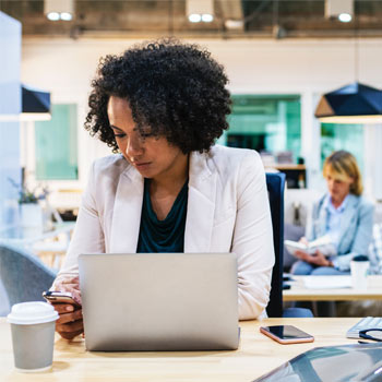 Businesswoman using laptop and mobile phone in working eenvironment