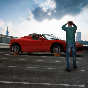 Sports car, tyres removed, standing on bricks - despairing owner standing in foreground