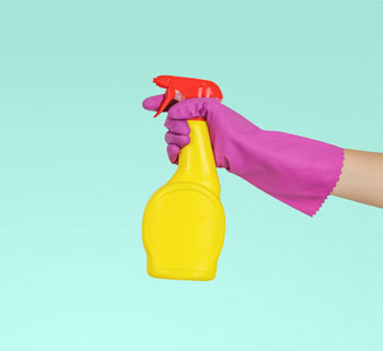 Arm, wearing marigold glove, holding unbranded cleaning spray