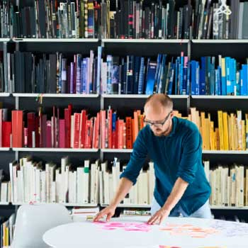 A designer, at a round table, with multicoloured books in the background.