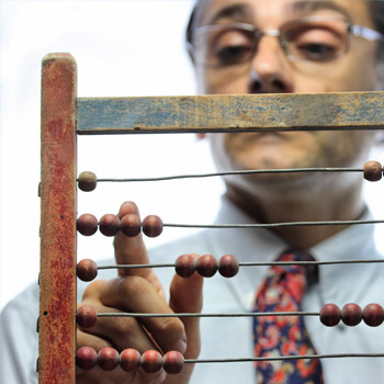 Man counting costs on an abacus