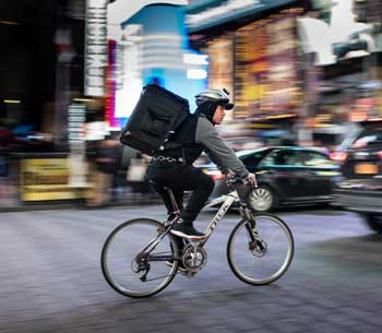 Pushbike courier cycling through busy city
