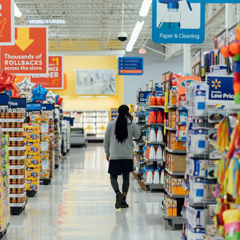 Woman, standing in supermarket aisle, surrounded by CPG/FMCG (packaged goods) items