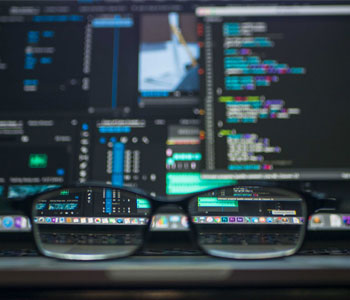 many screens with code, out of focus, with a pair of glasses on the desk in front, bringing a small portion into focus.