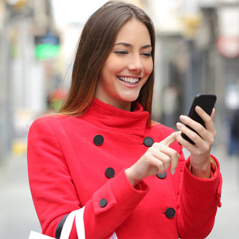 A woman smiling at her smartphone