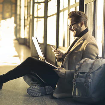 Businessman, casually dressed, with phone and laptop, sat on the floor of a public indoor space, consuming content - happy