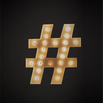 Lit hashtag sign on a dark background