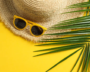 Sun hat, sunglasses, and palm leaf - evoking holidays