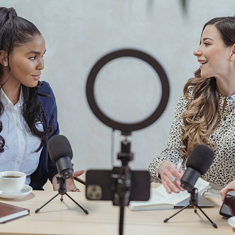 Two female influencers, recording a conversation, possibly for a podcast