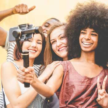 A group of young people holding a phone, taking a selfie