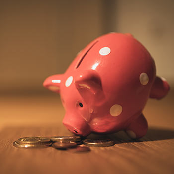 A porcelain piggy bank, apparently upended, with coins scattered around