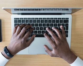Persons hands on laptop keyboard, preparing to type a subject line