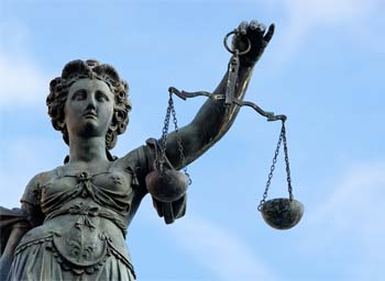 Lady Justice statue holding balancing scale to symbolise the law