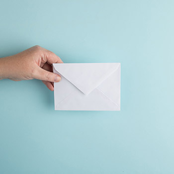 Person's hand holding a paper envelope