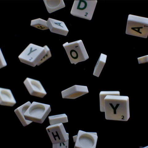Abstract - Plastic letter tiles from a word game, falling from the sky on a black background
