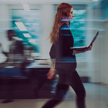 Office worker, with laptop, walking through office, at speed