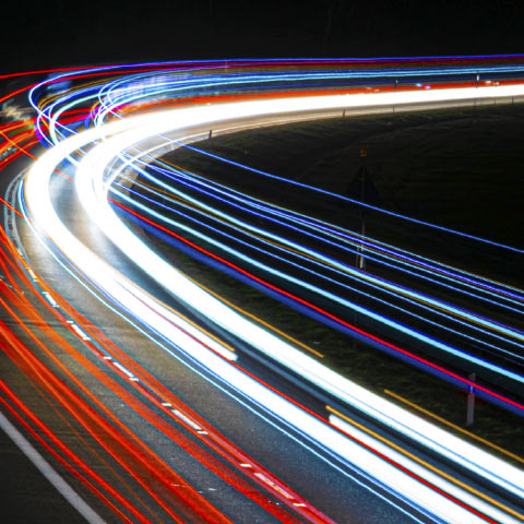 slow exposure time-lapse of lights on a road, to symbolize the fast flow of traffic