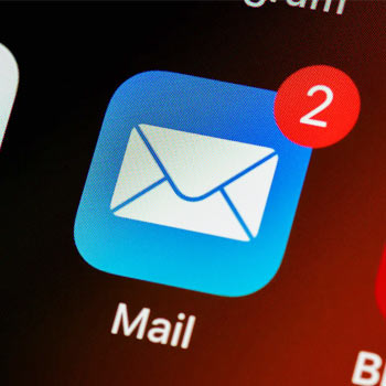 Close-in photo of an email icon on a phone homescreen