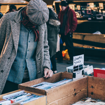 Person browsing market, books in old boxes - authentic experience
