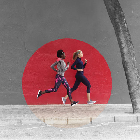 Two women, dressed in fitness apparel, running, along a pavement, with a tree in the foreground, with a spotlight shone on them