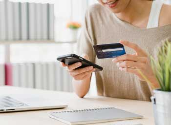 Woman with credit card and phone, using mobile banking