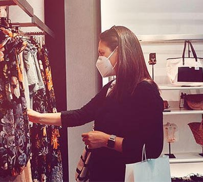 Fashionable woman, wearing a facemask, browsing a rail of clothes in a clothes shop, with handbags in the background