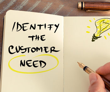 "Hand, holding fountain pen, having written ""Identify the customer need"" on lined pad, with hand-drawn picture of a lit lightbulb"