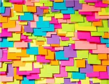 Hundreds of postit notes stuck on a wall