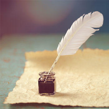 Feather quill in an ink pot, on some parchment paper, ready to write a letter