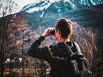 Person with binoculars searching mountainside