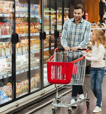 Adult and child, pushing shopping cart in supermarket aisle