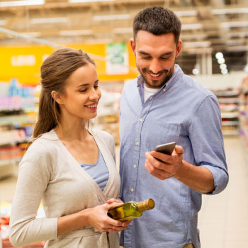 Happy couple shopping in-store, examining product, with phone