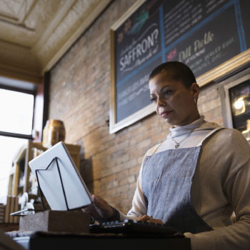 Small business owner in cafe, using tablet, working