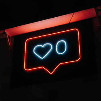Real neon sign - speech bubble with like symbol and 0.