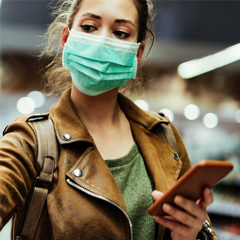 Shopper wearing protective face mask, using phone