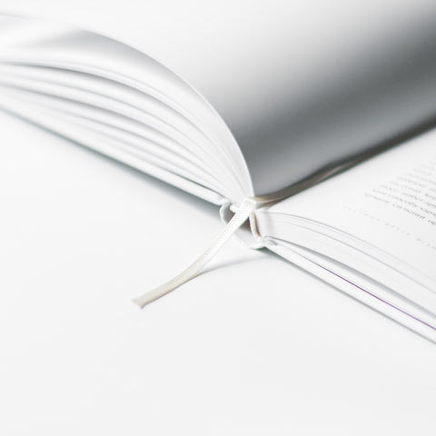 A white book, on a white background, laid open at an angle