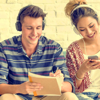 Two young people consuming media through digital devices, smiling