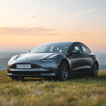 Electric car against sunset, in field
