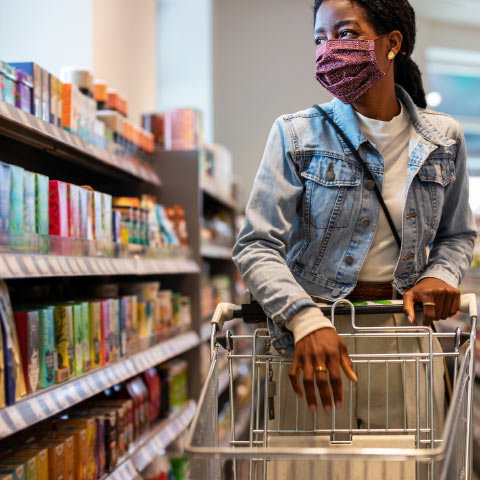 Shopper, in supermarket, with shopping cart, wearing mask, browsing products on a shelf