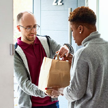 Delivery - man handing over paper bag (containing a purchase) to another man at his front door