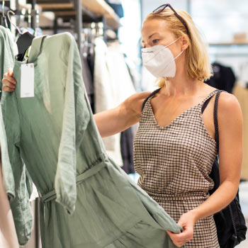 Woman, wearing face mask, examining a garment in a shop
