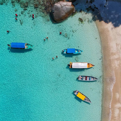 Boats on turquoise water, with sand - holiday sunshine